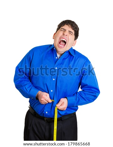 Closeup portrait of young frustrated, stressed man trying to pull measuring tape around paunch, but unable to because of size, isolated white background. Negative emotion facial expression feelings - stock photo