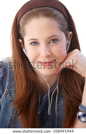 Closeup portrait of young ginger girl, smiling, listening to music through headphones. - stock photo