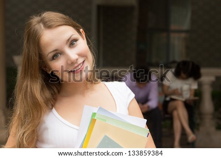 Closeup portrait of young girl with books outdoor. Students outside school holding books and smiling - stock photo