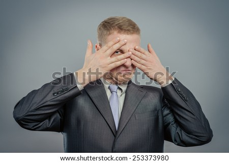 Closeup portrait of young guy, man, student, boy, worker, employee,  closing eyes with hands, can't see, hiding, isolated on white background. See no evil concept. Human emotions facial expressions - stock photo