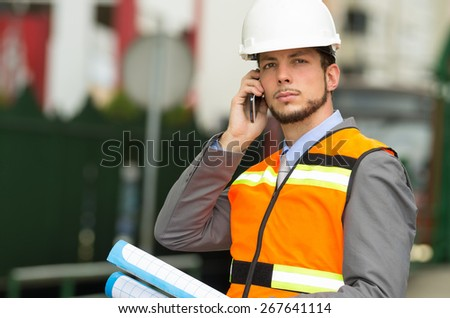 closeup portrait of young handsome architect supervising a construction using cell phone wearing helmet - stock photo