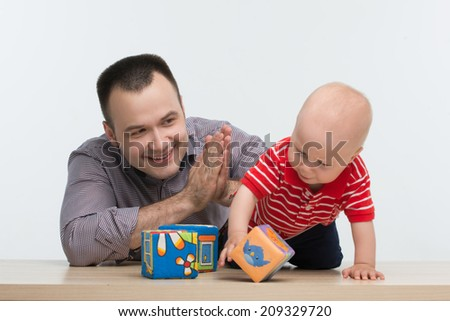 Closeup portrait of young handsome Caucasian happy father playing with his toddler son with colorful blocks, isolated on white - stock photo