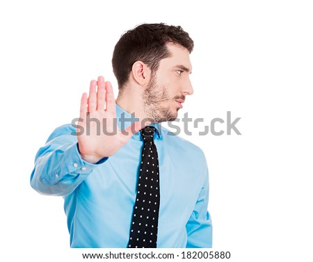 Closeup portrait of young handsome, grumpy man with bad attitude giving talk to hand gesture with palm outward, isolated white background. Negative emotions, facial expression feelings, body language - stock photo