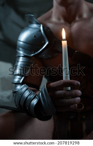 Closeup portrait of young handsome muscular man Gladiator in armour  holding candle against dark background, selective focus - stock photo