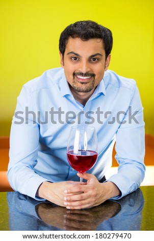 Closeup portrait of young happy, smiling business man with glass of red wine standing at bar, isolated on yellow, green background. Positive human emotion facial expression reaction, leisure, vacation - stock photo