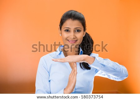 Closeup portrait of young happy smiling woman showing a time out gesture with hands isolated on orange background. Negative emotion facial expression feelings, body language - stock photo
