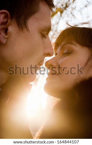 Closeup portrait of young kissing couple at sunshine