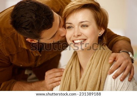 Closeup portrait of young loving couple. Man kissing woman. - stock photo