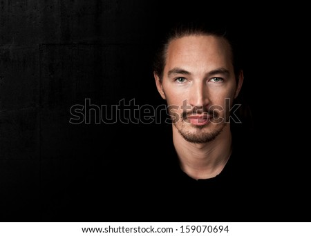 Closeup portrait of young man above black wall background - stock photo