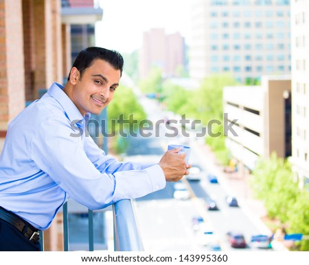 Closeup portrait of young man enjoying a drink while standing outside on his balcony, isolated on city background - stock photo