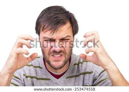 Closeup portrait of young man having a nervous crisis against white background - stock photo