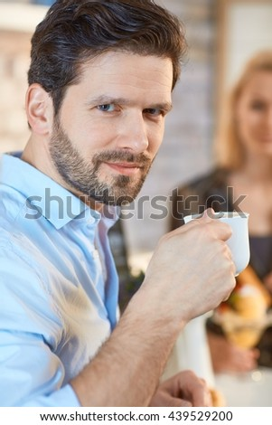 Closeup portrait of young man holding coffee cup, drinking, looking at camera with small smile. - stock photo