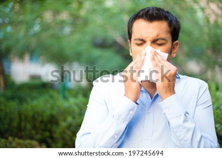 Closeup portrait of young man in blue shirt with allergy or cold, blowing his nose with a tissue, looking miserable unwell very sick, isolated outside green trees background. Flu season, vaccination. - stock photo
