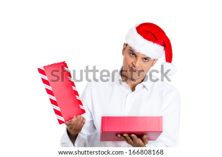 Closeup portrait of young man in red santa claus hat opening gift and very upset at what he received, isolated on white background with space to left. Negative human emotion facial expression - stock photo