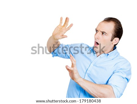 Closeup portrait of young man looking shocked scared trying to protect himself from unpleasant situation or object thrown at him, isolated white background. Negative emotion facial expression feeling - stock photo