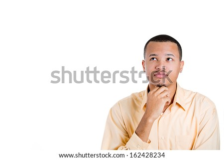 Closeup portrait of young man thinking daydreaming deeply about something with hand on chin looking upwards, isolated on background with copy space to left. Human facial expressions signs and symbols - stock photo