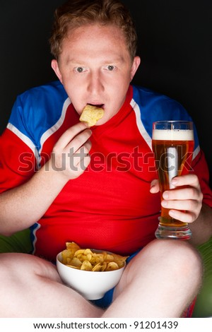 Closeup portrait of young man wearing sportswear fan of football team is watching tv and rooting for his favorite team. Sitting on beanbag alone at night drinking beer and eating chips.