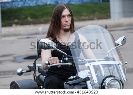 Closeup portrait of young man with long hair riding a motorcycle - stock photo