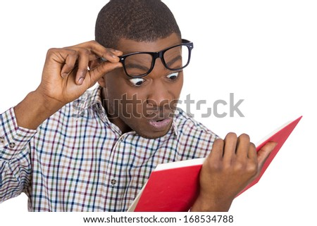 Closeup portrait of young man, with wide opened eyes staring at a book page, shocked, surprised by the twists and turn of story, isolated on white background. Human emotion, facial expression, feeling - stock photo