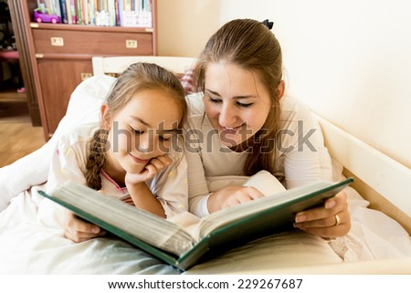 Closeup portrait of young mother and daughter lying in bed and viewing photo album