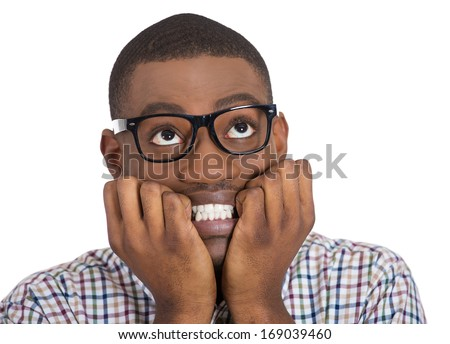 Closeup portrait of young nerdy, unhappy, scared guy, student with black glasses biting nails, looking up with a craving for something, anxious, worried, isolated on white background. Face expression - stock photo