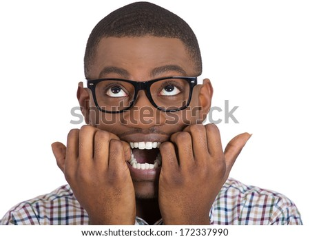 Closeup portrait of young nerdy, unhappy, scared man, student with big glasses biting nails, looking up with a craving for something, anxious, worried, isolated on white background. Face expression - stock photo
