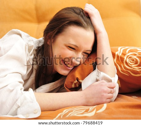 Closeup portrait of young pretty girl laying on her bed at her modern stylish apartment. Laughing - stock photo