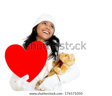 Closeup portrait of young pretty woman wearing winter gear attire sweater holding red valentine heart and teddy bear looking up, isolated white background. Positive emotion facial expression feelings. - stock photo