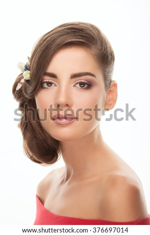 Closeup portrait of young romantic brunette woman with flower headpiece and cute makeup in read blouse calm looking into camera posing on white studio background