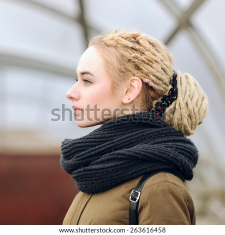 Closeup portrait of young serious beautiful blonde woman with a dreadlocks bun hairstyle - stock photo