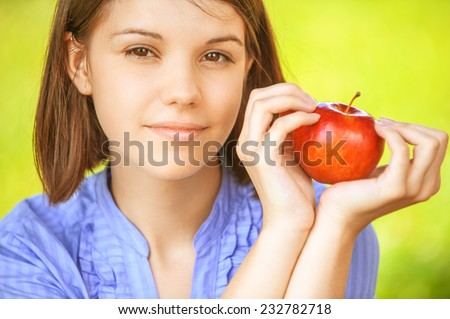 Closeup portrait of young smiling brunette woman holding red apple at summer green park - stock photo