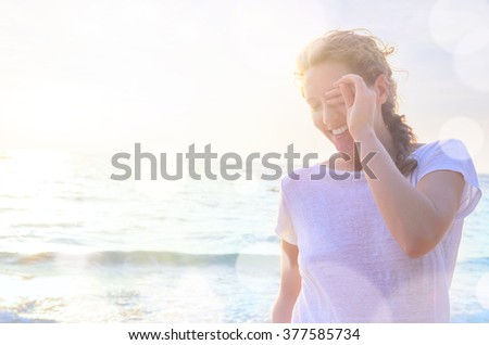 Closeup portrait of young smiling caucasian woman at the beach - stock photo