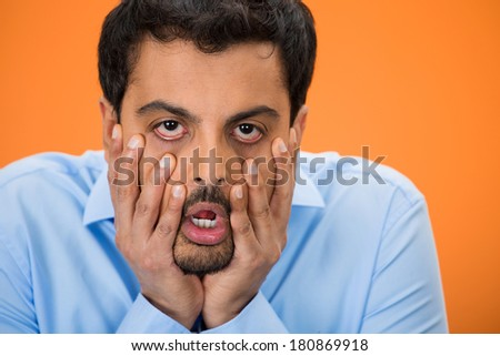 Closeup portrait of young tired, fatigued man worried and stressed, dragging face down with hands, isolated on orange background. Negative human emotion facial expression feelings - stock photo