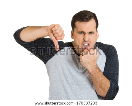 Closeup portrait of young unhappy, annoyed, sick man putting finger in mouth showing something sucks with thumbs down, isolated on white background.  Negative emotions, feelings, facial expressions.