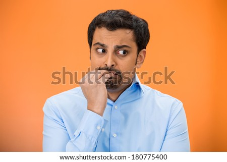 Closeup portrait of young unhappy man, biting his nails looking away with craving for something, anxious, worried isolated on orange, red background. Negative emotions, facial expression, feelings