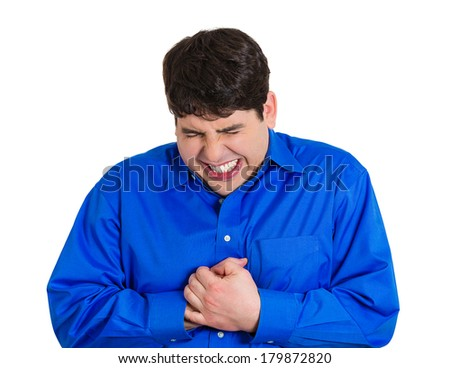 Closeup portrait of young, unhappy, stressed man in burning pain, clutching chest from pain, pressure, tightness, isolated on white background. Negative emotion facial expression feelings. - stock photo
