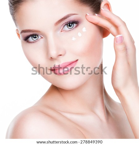 Closeup portrait of young woman applying cream on her pretty face - on a white background. - stock photo
