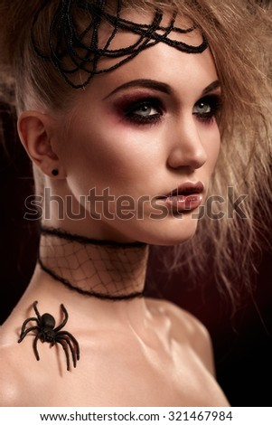 Closeup portrait of young woman in halloween makeup with spider on shoulder, looking away. - stock photo