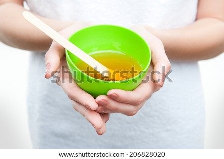 Closeup portrait of young woman in towel preparing natural homemade organic facial mask of honey, isolated on white - stock photo