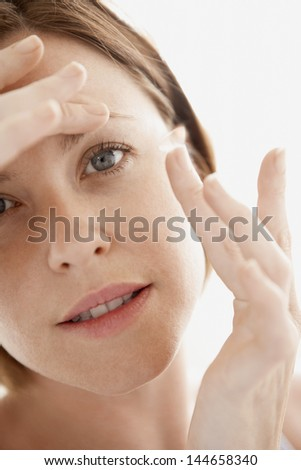 Closeup portrait of young woman inserting contact lens isolated on white background - stock photo