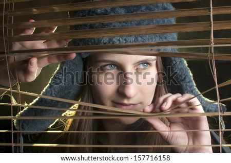 Closeup portrait of young woman looking through window  - stock photo