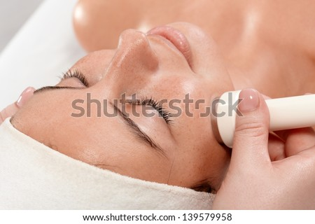 Closeup portrait of young woman receiving facial beauty treatment, laying eyes closed. - stock photo