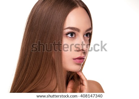 Closeup portrait of young woman showing gorgeous care for face with bare shoulders on white studio background. - stock photo