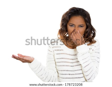 Closeup portrait of young woman with disgust on her face, covers pinches nose looks at you, something stinks, very bad smell, situation, isolated on white background. Human emotion, face expression. - stock photo