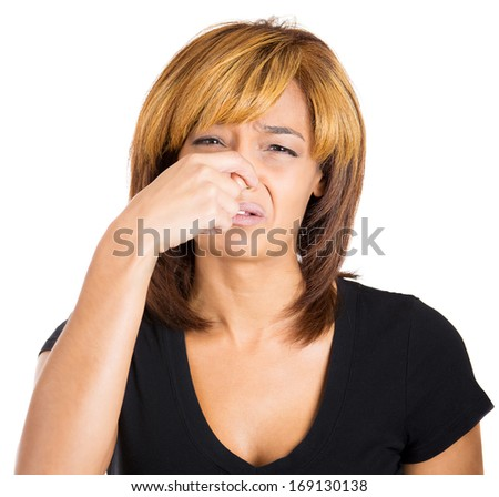 Closeup portrait of young woman with disgust on her face who covers pinches her nose looks at you, something stinks, very bad smell, situation, isolated on white background. Human emotion, expression. - stock photo