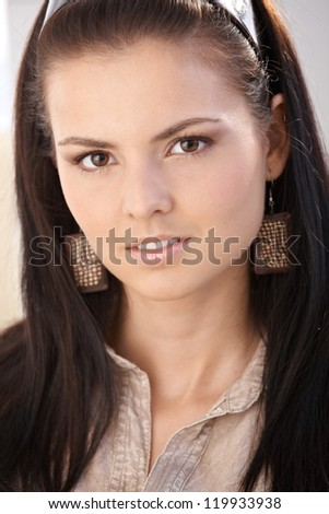 Closeup portrait of young woman with long hair, looking at camera. - stock photo