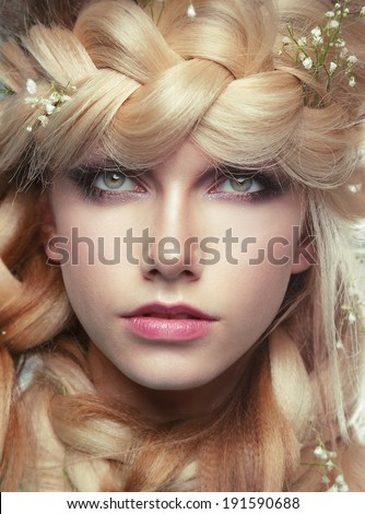 Closeup Portrait of Young Woman with Tress and Flowers - stock photo