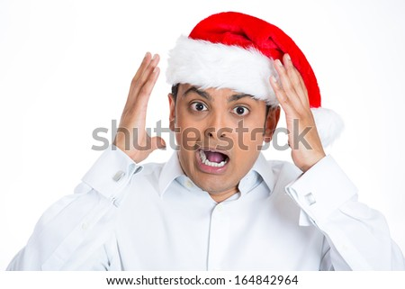 Closeup portrait of young worried stressed man in red santa claus hat, hands in air screaming open mouth, isolated on white background with space to left. Negative human emotion facial expression