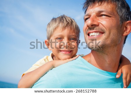 Closeup portrait og father holding son on his shoulders at the beach - stock photo