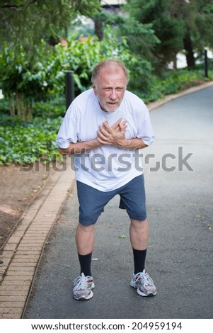Closeup portrait, old man clutching chest, having heart pain, after strenuous workout, isolated outdoors, green trees background. Myocardial infarction, aortic aneurysm rupture - stock photo